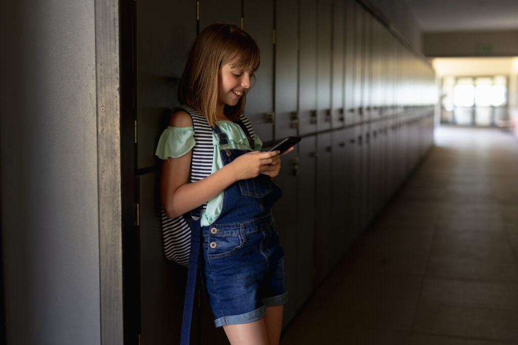 Schoolgirl leaning against lockers in a corridor using a smartphone